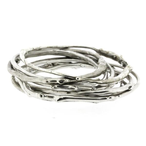 A large stack of sterling silver bangle bracelets that have a smooth organic texture that looks as if they are twigs covered in ice.
