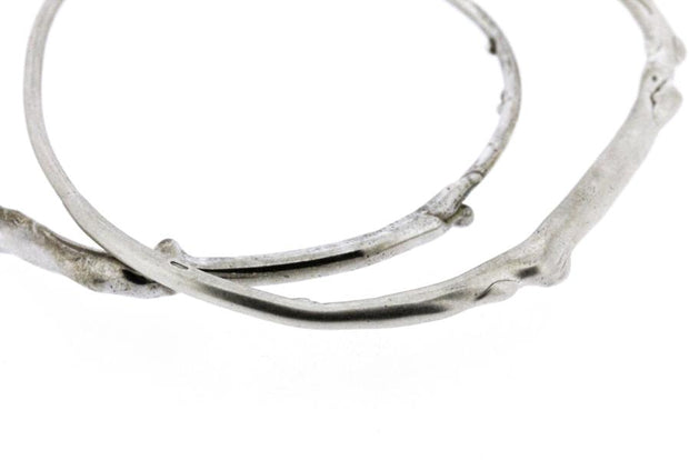 A detail photo of two sterling silver bangle bracelets that have a smooth organic texture that looks as if they are twigs covered in ice.
