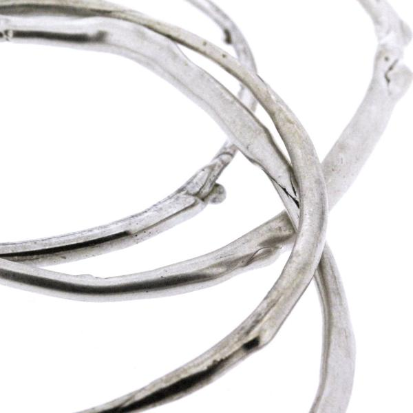 A detail photo of a stack of sterling silver bangle bracelets that have a smooth organic texture that looks as if they are twigs covered in ice.