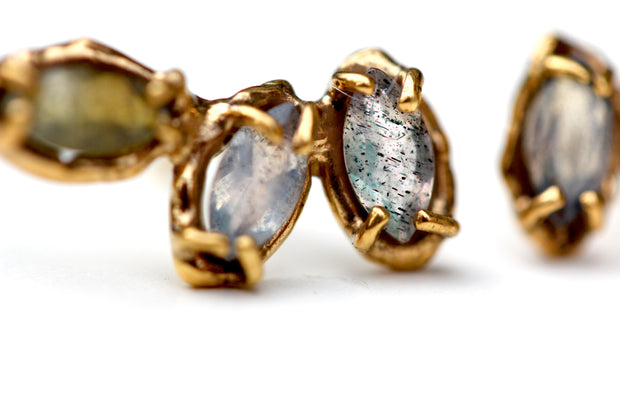 Detail photo of gold earrings with labradorite stones set with organic prongs.