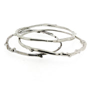 A set of three sterling silver bangle bracelets that have a smooth organic texture that looks as if they are twigs covered in ice.