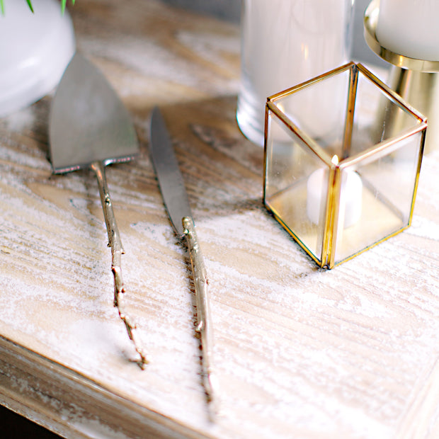 Handmade Sterling and Brass Cake Servers with Branch Handles and Hammered Texture on tabletop decorated for a wedding.