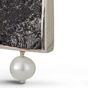 Close up detail photo of a square raw surface black tourmaline gemstone with a pearl accent.