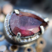 Detail photo of a pear-shaped red tourmaline gemstone set in blackened sterling silver.