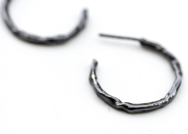 Detail photo of a blackened silver hoop earring with an organic vine-like texture.
