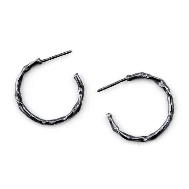 Small hoop earring featuring organic texture resembling a twig or vine.