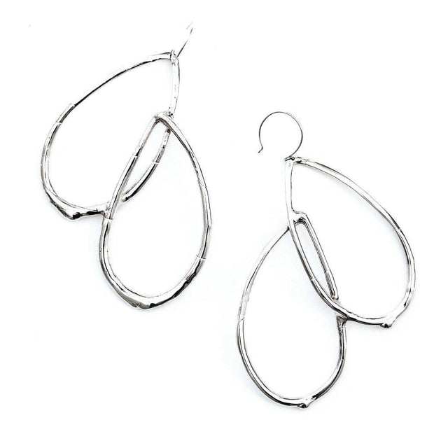 An statement earring featuring curved tear-drop shaped forms with an organic texture resembling a smooth twig or vine.
