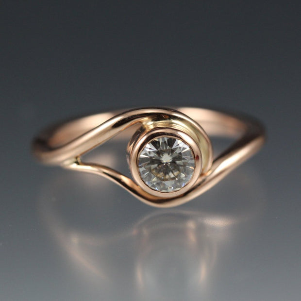 Rose Gold and Moissanite Engagement Ring, the metal gently wraps around the stone, like a vine or wave.
