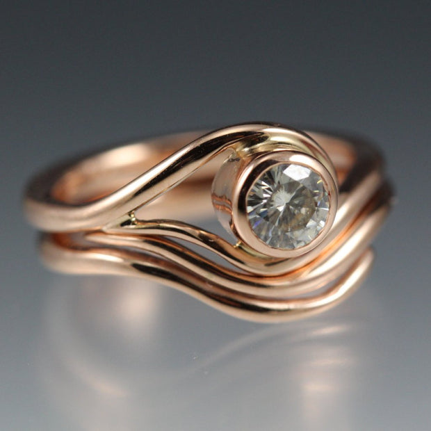 Rose Gold and Moissanite Engagement ring and nesting wedding band that have a vine or wave appearance.