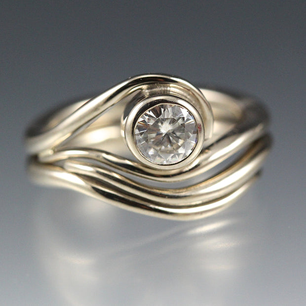 White Gold and Moissanite Engagement ring and nesting wedding band that have a vine or wave appearance.