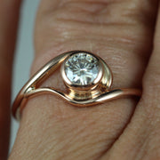 A contemporary and unique, vine-like engagement ring on a finger