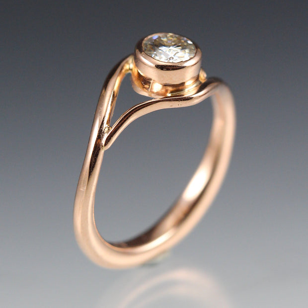 Side view of a Rose Gold and Moissanite Engagement Ring, the metal gently wraps around the stone, like a vine or wave.