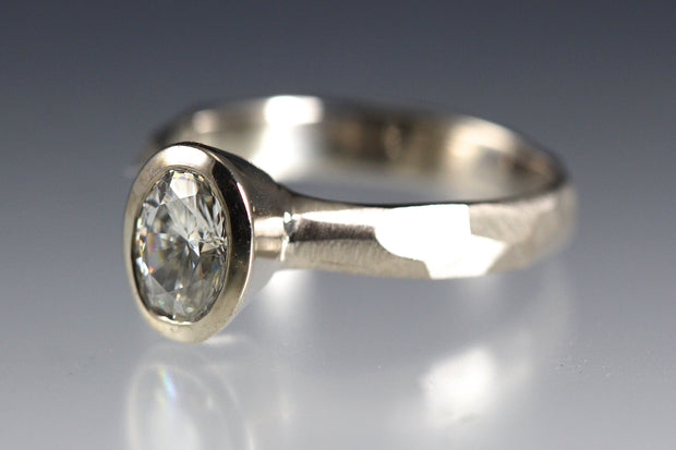 Bezel Set Oval Moissanite Engagement Ring featuring a organic faceted band in 14k white gold