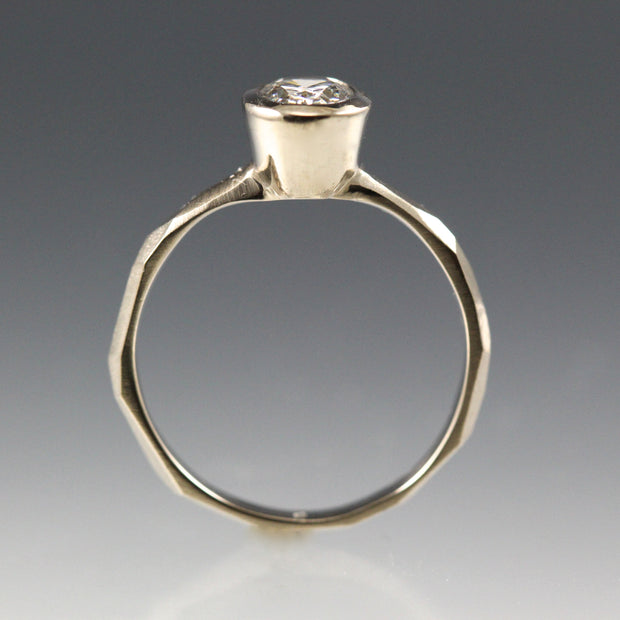 Side view of a 14k white gold Bezel Set Oval Engagement Ring featuring a organic faceted band.