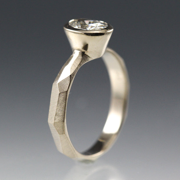 Side view of a Bezel Set Oval Engagement Ring featuring a organic faceted band in 14k white gold