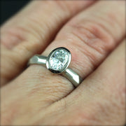 Bezel Set Oval Engagement Ring featuring a organic faceted band on a woman's hand.
