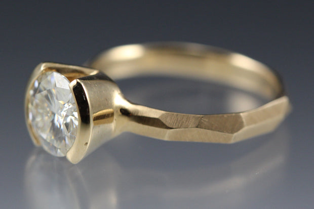 Side view of a Modern 14k yellow gold Engagement Ring with a Partial Bezel containing a Moissanite Stone with a faceted band.