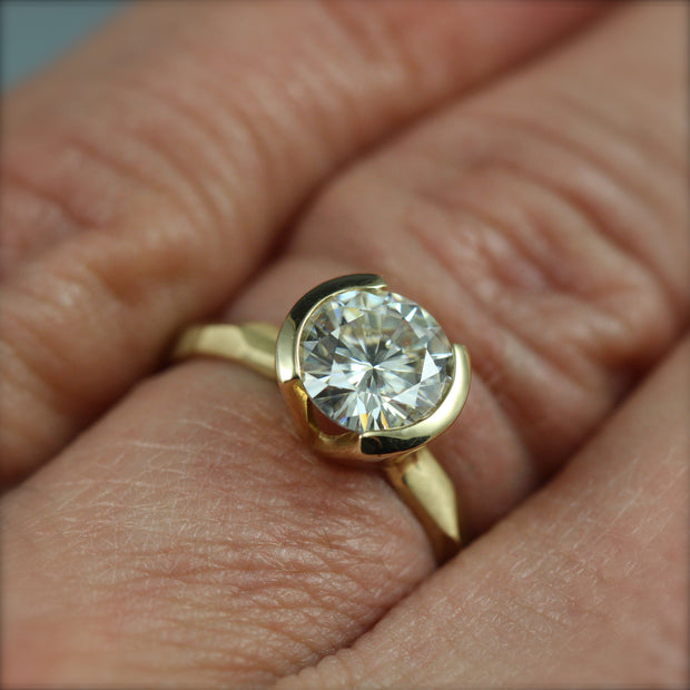 A contemporary partial bezel engagement ring on a woman's hand.