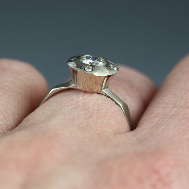A contemporary halo style engagement ring on a woman's hand, featuring a center Moissante and 4 small stones in North, south, east west positions