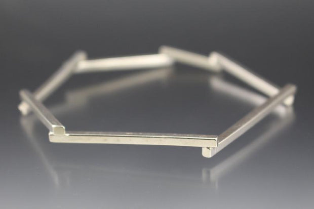 A geometric shaped, silver bangle bracelet.
