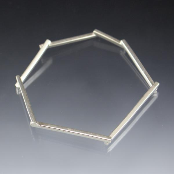 A single silver bangle bracelet that shaped in an amorphous geometric shape.