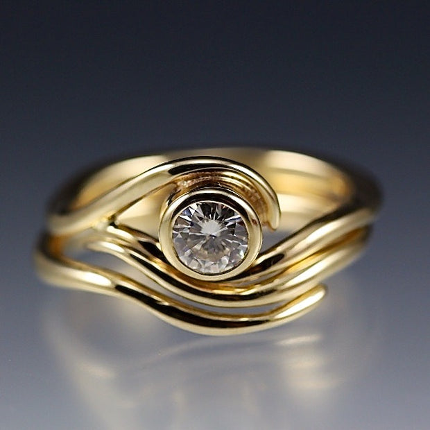 Yellow Gold and Moissanite Engagement ring and nesting wedding band that have a vine or wave appearance.