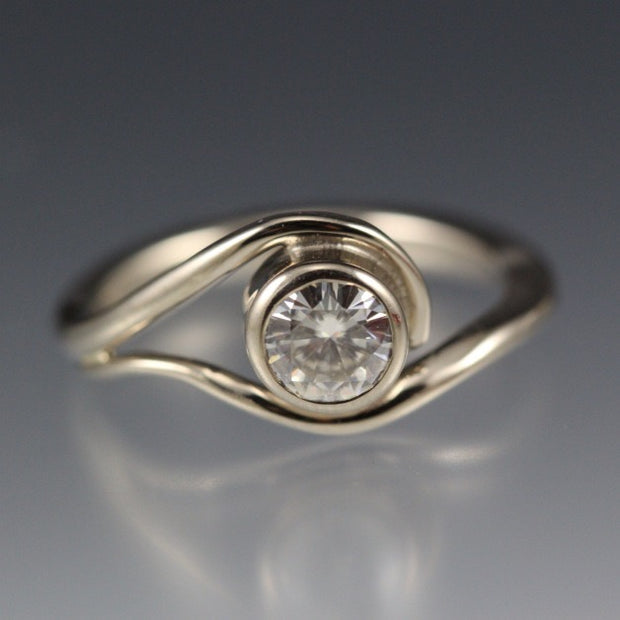White Gold and Moissanite Engagement Ring, the metal gently wraps around the stone, like a vine or wave.