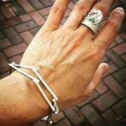 A woman's wrist and hand wearing a stack of silver bangle bracelets and a large silver ring.