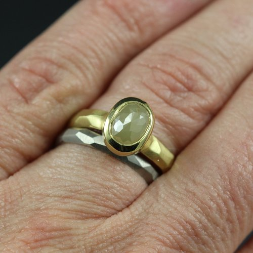 A yellow gold ring with a yellow rose cut diamond and a white gold ring on a woman's hand.