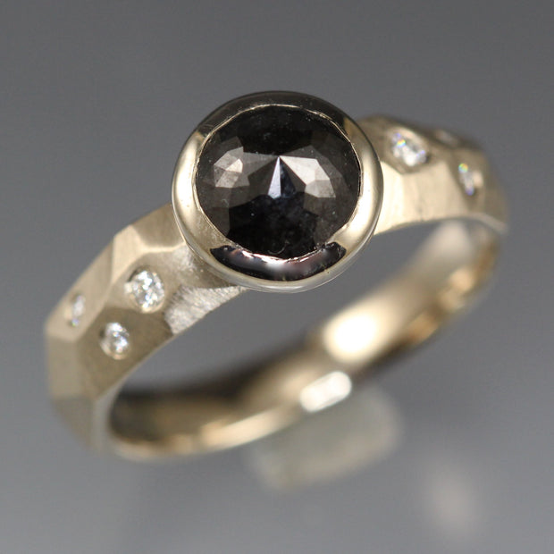 A bezel set black rose cut diamond ring accented with white flush set diamonds.