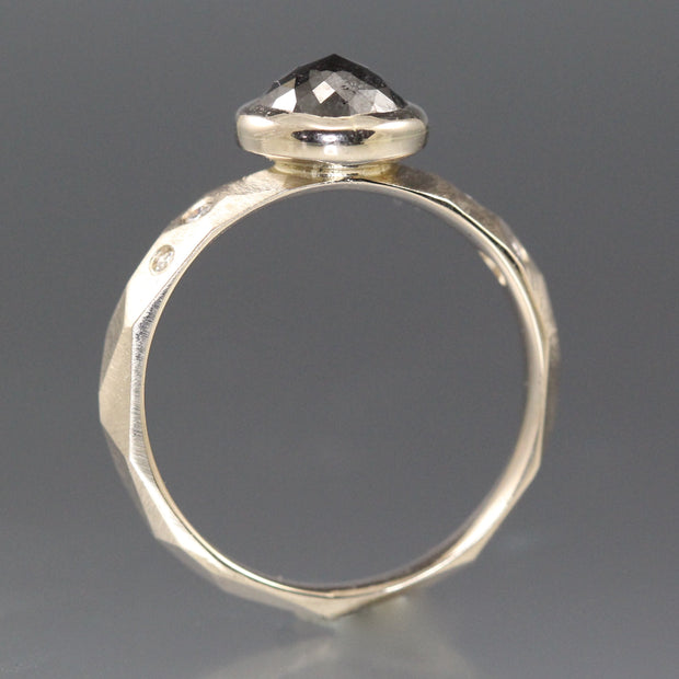 Side view of a white gold ring with a natural black rose cut diamond.