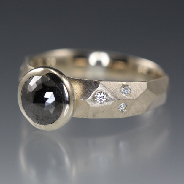 A white gold ring with a bezel set black rose cut diamond.
