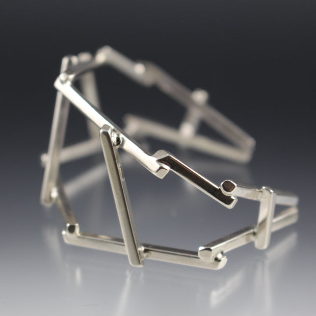Side view of a architectural, bridge-like sterling silver cuff bracelet.