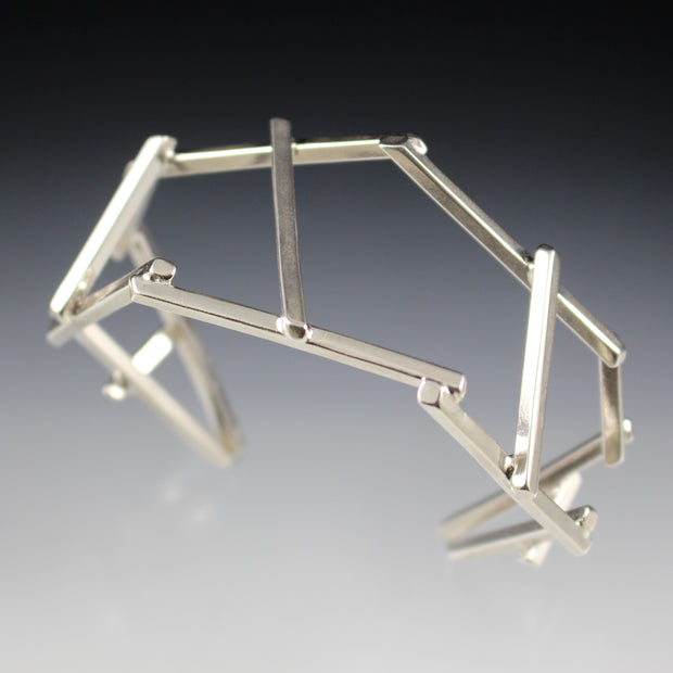 Top view of a dramatic, architectural sterling silver cuff bracelet.