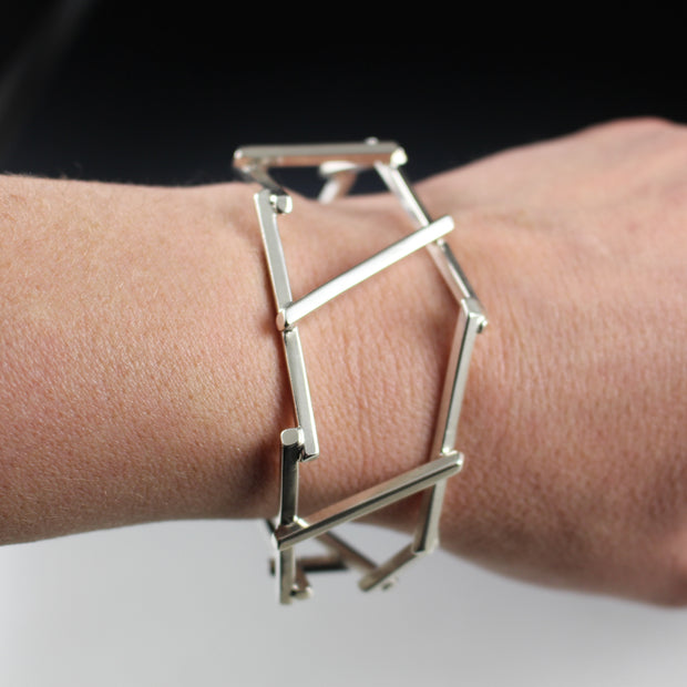 A woman's wrist wearing a dramatic, architectural sterling silver cuff bracelet.