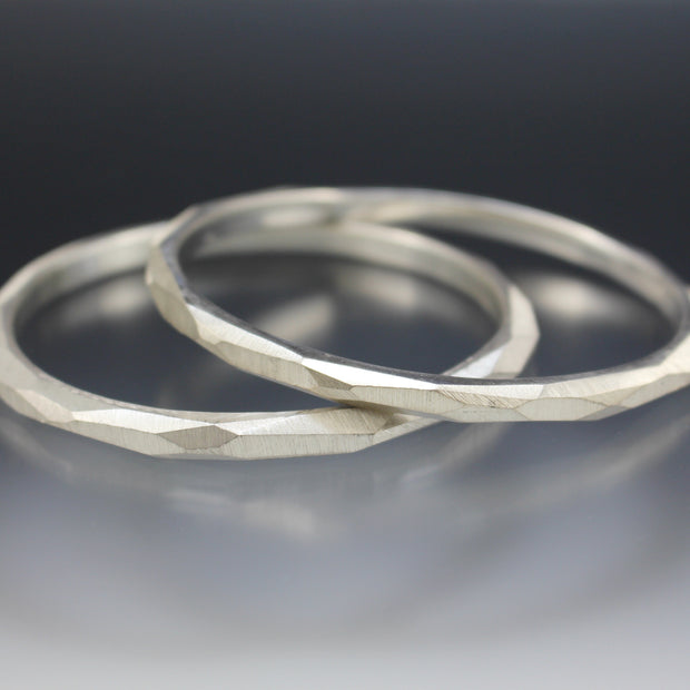 Two sterling silver bangle bracelets that have a faceted surface texture.