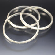 A cluster of three sterling silver bangle bracelets that have a faceted texture.