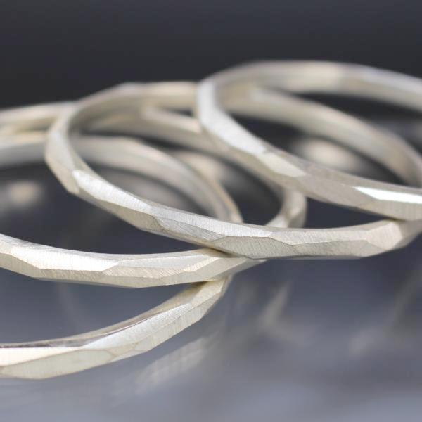 A stack of sterling silver bangle bracelets that have a faceted texture.