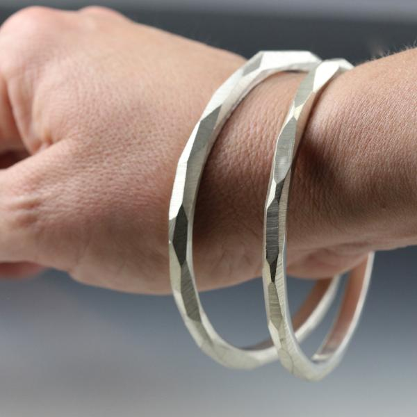 A woman's wrist wearing two sterling silver bangle bracelets that have a faceted texture.