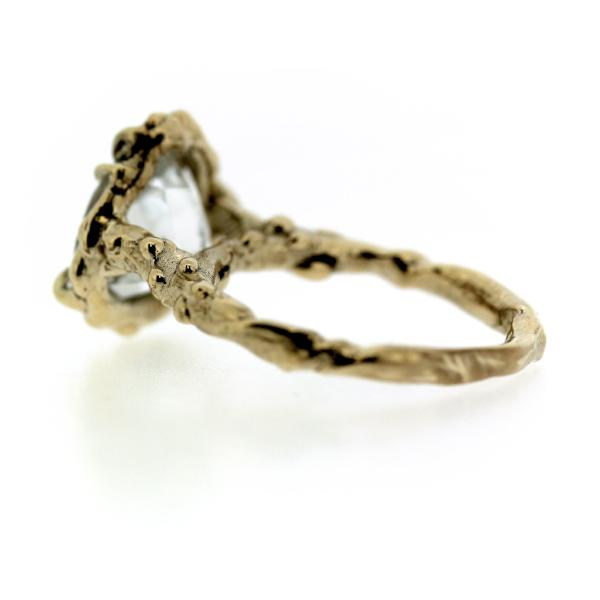 Back view of an organic inspired ring made in 14k yellow gold and trillion-shaped white topaz