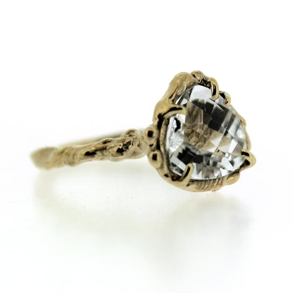 Side view of an organic inspired ring made in 14k yellow gold and trillion-shaped white topaz