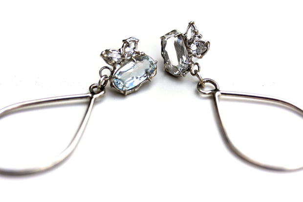 Sterling silver dangle earrings with a cluster of white topaz gemstone in various shapes and a tear drop shaped dangle.
