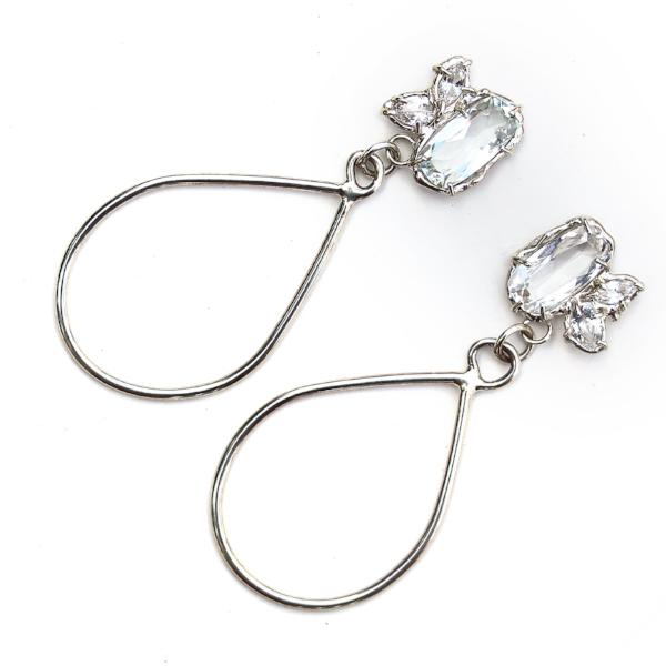 Sterling silver dangle earrings with three white topaz gemstone in various shapes and a tear drop shaped dangle.