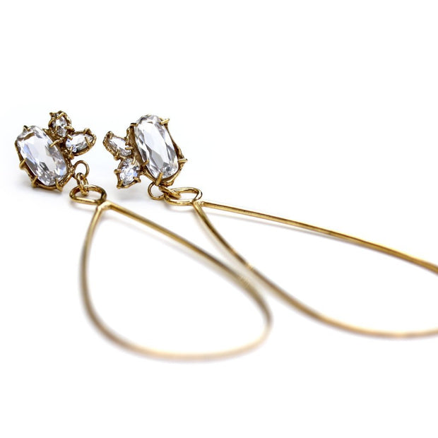 Long, gold statement earrings with a cluster of white topaz gemstones at the top and a tear drop shaped dangle.