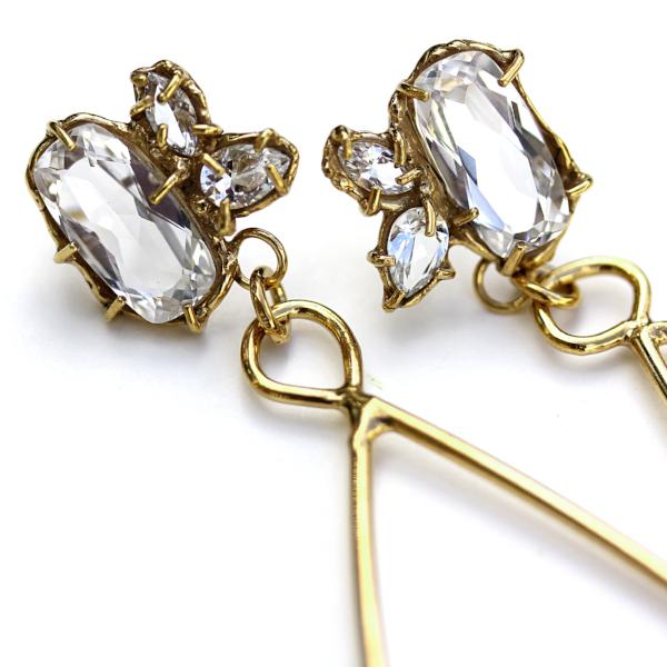 Detail photo of the top section of a pair of gold earrings a cluster of three white topaz gemstone set in an organic prong setting.