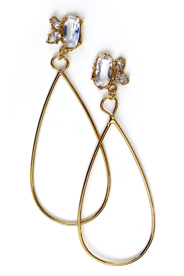 Long, gold statement earrings with a cluster of white topaz gemstone in various shapes at the top and a tear drop shaped dangle.