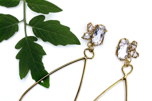 Detail photo of the top section of a pair of gold earrings a cluster of three white topaz gemstone set in an organic prong setting with a plant in the background.