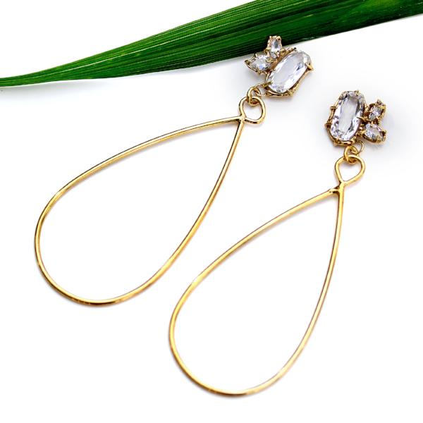 Gold dangle earrings with three white topaz gemstone in various shapes and a tear drop shaped dangle with a green plant leaf in the background.