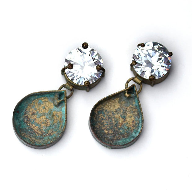 A pair of earrings with a sparkling CZ on top and an Powder coated and Patinated Copper tear drop shape dangle.