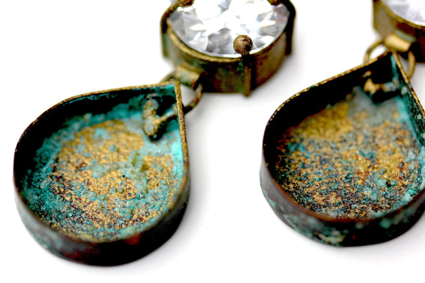Detail photo of a pair of earrings with an earthy blue and gold colored Patina.
